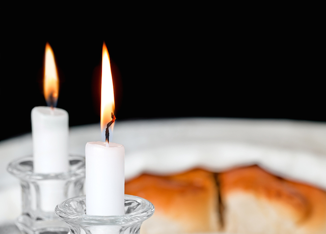 Shallow depth of field close up. Focus on front candle flame and wick. Copyspace. Isolated on a black background.