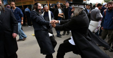 Ultra orthodox Jews dance in the street near the tomb of Rabbi Nachman of Breslov before the Jewish new year in the Ukrainian city of Uman September 22, 2006. Every year thousands of Jewish pilgrims travel to Nachman's tomb in Uman on Rosh Hashana, the Jewish new year, which begins on Friday evening.   REUTERS/Gil Cohen Magen (UKRAINE)